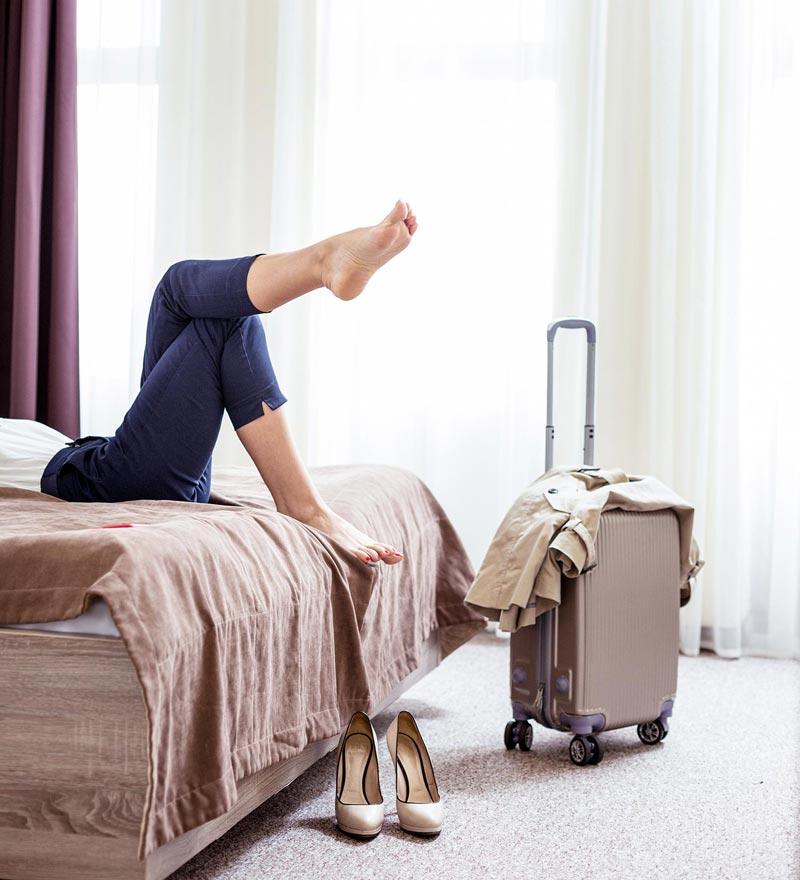 Frau im Hotelzimmer mit Koffer