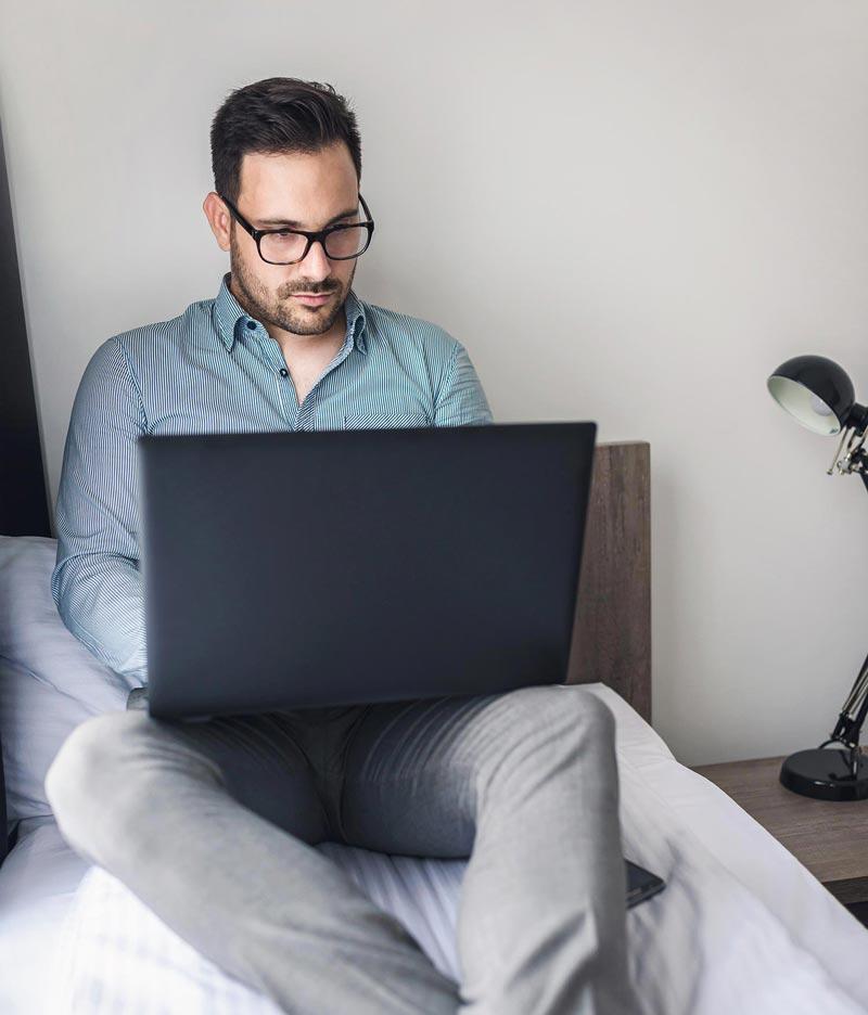man laptop bed