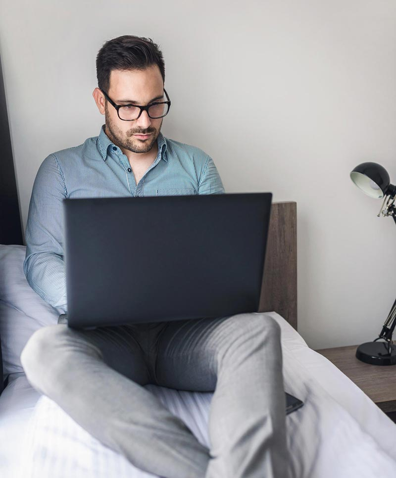 Man on bed with laptop